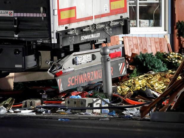 Corpos de vítimas são cobertos por um plástico amarelo ao lado de destroços após um caminhão invadir uma feira de Natal em Berlim, na Alemanha (Foto: Pawel Kopczynki/Reuters)
