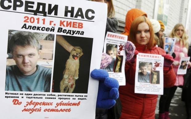 Ativistas protestam diante de tribunal em que Oleksiy Vedula era julgado nesta segunda-feira (13) em Kiev, capital da Ucrânia. O adolescente é acusado de ter matado dezenas de cães e postado na internet foto dos animais mortos. Ativistas dos direitos animais pediram uma pena rigorosa para Vedula (Foto: Reuters)