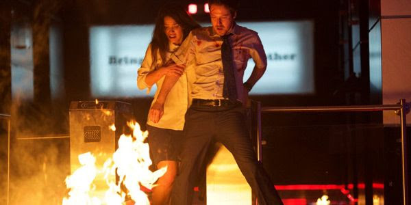 Mike Milch (John Gallagher Jr.) and Leandra Flores try to survive the murderous attempts made on their lives by fellow employees in THE BELKO EXPERIMENT.