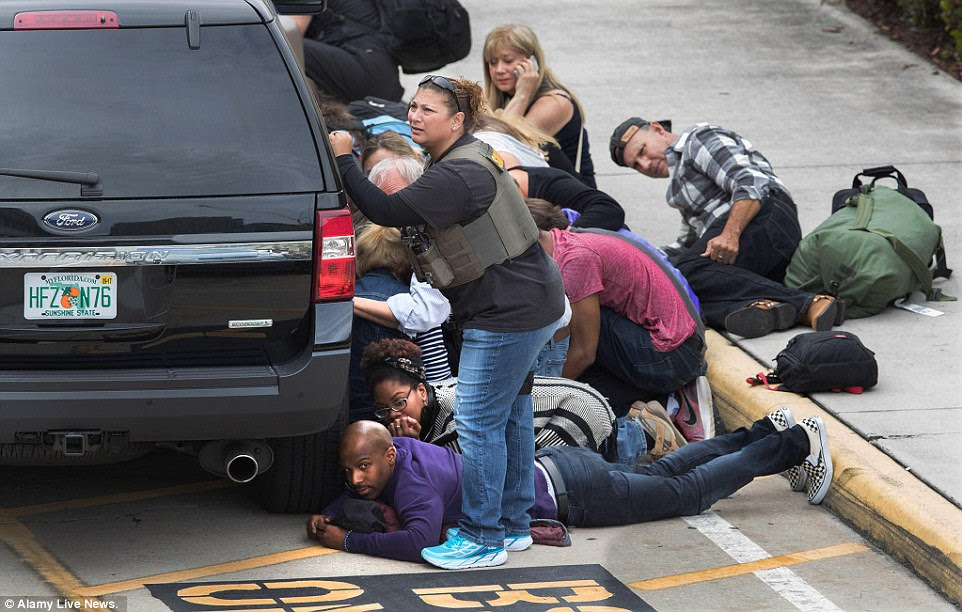 People take cover at the Ft. Lauderdale Airport after a gunman killed 5 people and injured many more