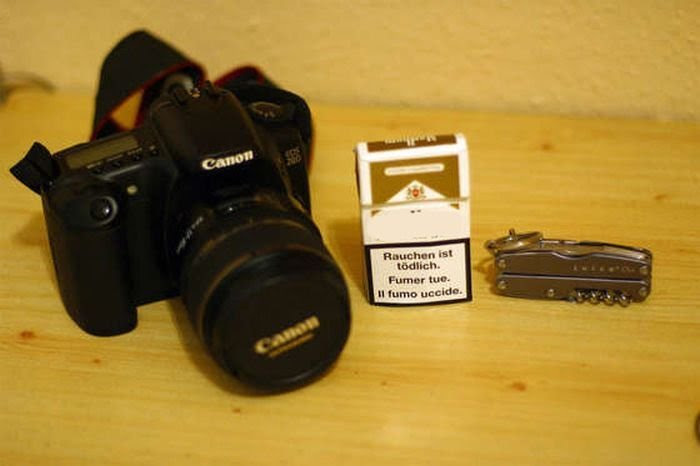Cámara profesional, cajetilla de cigarros y una navaja