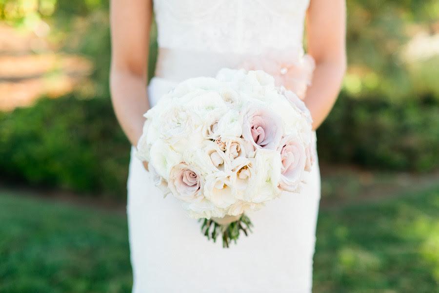bride wears lace wedding dress holds romantic bridal bouquet