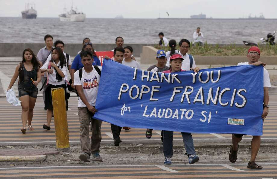 """Environmental activists carry a banner as they march towards a Roman Catholic church to coincide with Pope Francis' encyclical on climate change Thursday, June 18, 2015 in Manila, Philippines. In a high-level, 190-page document released Thursday, Francis describes ongoing human damage to nature as """"one small sign of the ethical, cultural and spiritual crisis of modernity."""" The solution, he says, will require self-sacrifice and a """"bold cultural revolution"""" worldwide. (AP Photo/Bullit Marquez) Photo: Bullit Marquez, Associated Press"""