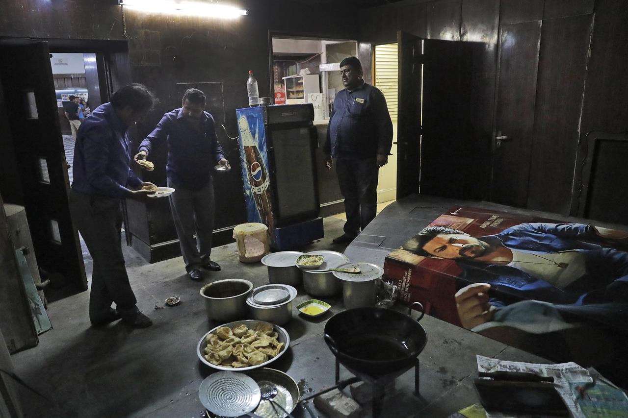 In this Thursday, March 30, 2017 photo, employees eat lunch together next to a Bollywood film poster at Regal Theater in New Delhi, India. From Bollywood superstars to political heavyweights, the theater had hosted some of India's biggest names over more than eight decades. But with nostalgic theater-goers singing their way to the exits after a final showing of a Bollywood classic, the iconic New Delhi theater has closed its doors to make way for a multiplex.