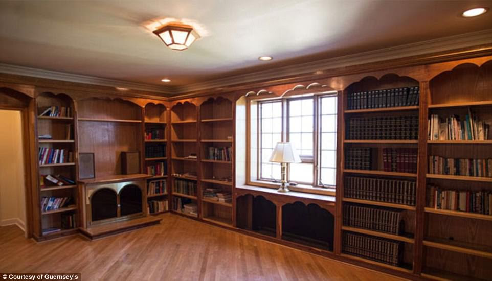 The seven bedroom, seven-and-a-half bath home, sits on 1.2 acres on Bluff Road, on the Palisades Cliffs overlooking the Hudson River and the Manhattan skyline. (pictured, wood-paneled library)