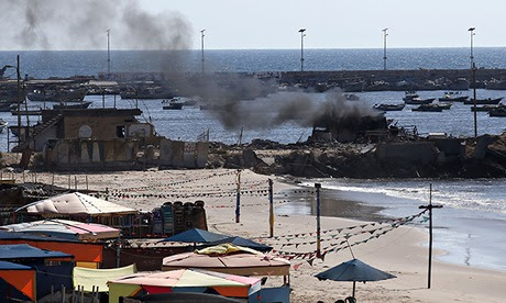 Smoke billows from a beach shack following an Israeli military strike - gaza port shelling