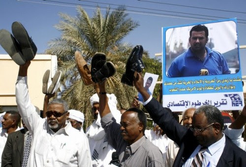 Journalists display their shoes and carry a poster of Iraqi journalist Muntazer al-Zaidi during a demonstration in Khartoum December 18, 2008. The journalists were taking part in the rally in support of al-Zaidi, who hurled his shoes at U.S. President George W. Bush during a news conference in Iraq on December 14, 2008. REUTERS/Mohamed Nureldin Abdallah (SUDAN)