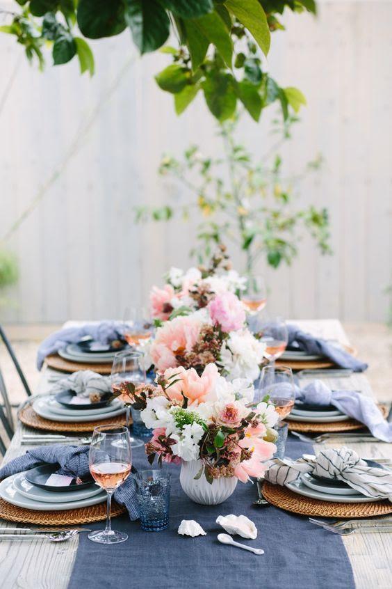 ein wedidng tablescape mit einer indigo Tischläufer, Gläser und Servietten und rosa Blumen