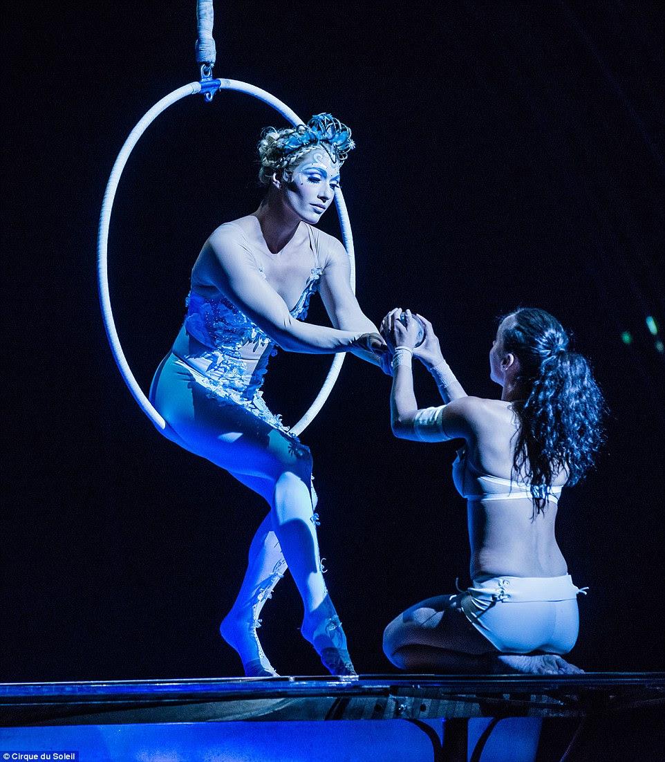 A deusa da lua executa acrobacias aéreas em um aro e, em seguida, chama uma mulher da água