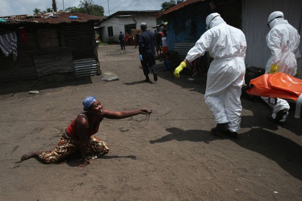 A woman throws a handful of soil towards the body of her sister as Ebola burial team members take her Mekie Nagbe, 28, for cremation on October 10, 2014 in Monrovia, Liberia. Nagbe, a market vendor, collapsed and died outside her home earlier in the morning while leaving to walk to a treatment center, according to her relatives. The burial of loved ones is important in Liberian culture, making the removal of infected bodies for cremation all the more traumatic for surviving family members. The World Health Organization says the Ebola epidemic has now killed more than 4,000 people in West Africa.