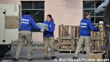 Three individuals in blue FEMA uniforms pass cartons to each other in front of a pink building (Photo: STAN HONDA/AFP/Getty Images)