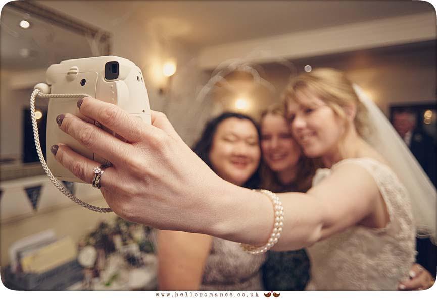Polaroid camera at wedding held by bride - www.helloromance.co.uk