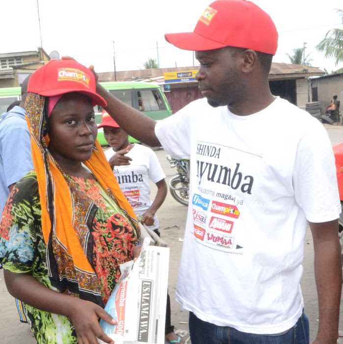 4.Mwanadada msomaji wa Gazeti la Uwazi akivalishwa kofia iliyoandikwa' Shinda Nyumba' kutoka kwa Yohana Mkanda baada ya kujaza kuponi yake ili kushirikid droo ya pili.-001