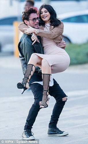 Seeing the funny side: Kylie giggled as he male pal hoisted her up during her appearance in Malibu