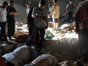 A handout image released by the Syrian opposition's Shaam News Network shows people inspecting bodies of children and adults laying on the ground as Syrian rebels claim they were killed in a toxic gas attack by pro-government forces in eastern Ghouta, on the outskirts of Damascus on August 21, 2013. (AFP/Shaam News Network)