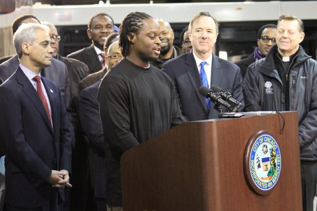 <p>Michael Russell, 38, stands with Mayor Rahm Emanuel (left), CTA President Forrest Claypool (second from right) and clergy as he talks about his experience as a rail apprentice.</p>
