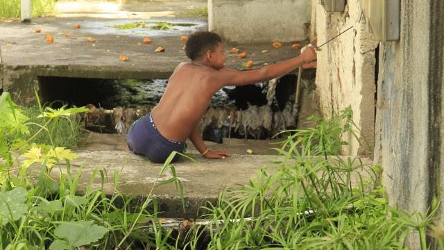 Menino descansa sobre a água suja