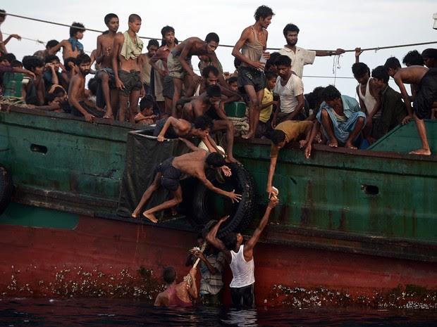 Imigrantes a bordo de um barco à deriva pegam alimentos jogados por um helicóptero do exército tailandês nas águas da ilha do sul de Koh Lipe, no mar de Andaman. Os passageiros disseram que várias pessoas morreram nos últimos dias (Foto: Christophe Archambault/AFP)
