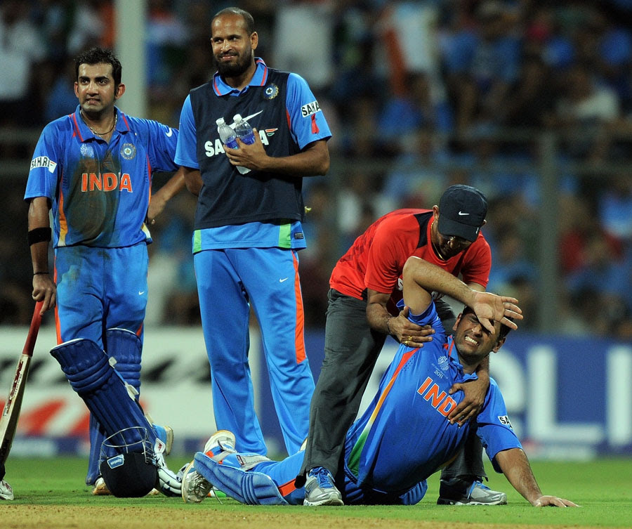 MS Dhoni is attended to after feeling some pain in his side