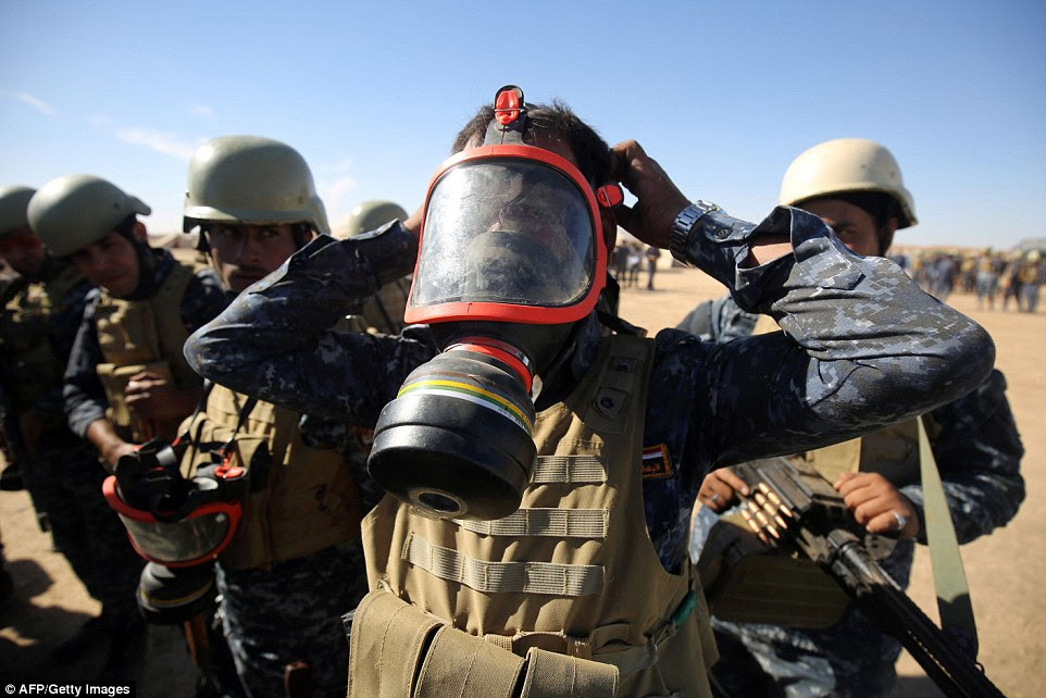 An Iraqi policeman in his gasmask, as they prepare for the battle ahead, which government official say will be 'bloody'
