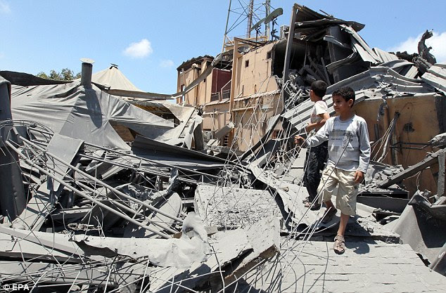 Innocent victims: Children inspect the rubble of what Libyan authorities claim was a hotel damaged by a Nato airstrike on Thursday