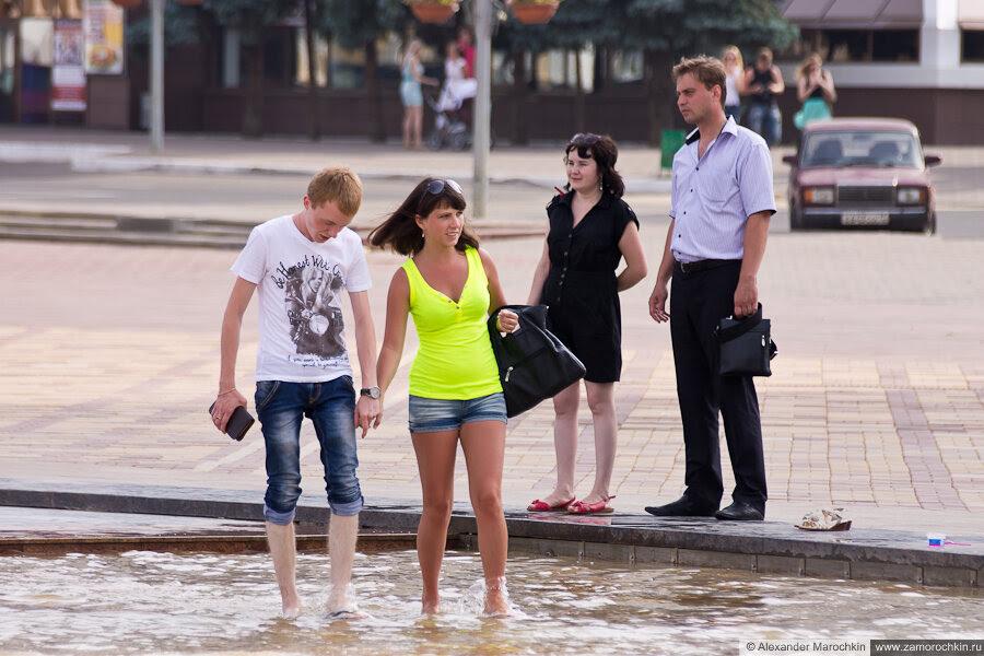 Парочка гуляем босиком в пешеходной зоне фонтана
