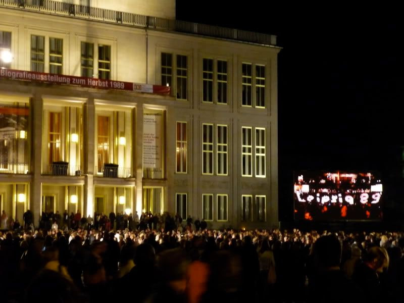 "The opera house, the crowd, and the screen with ""Leipzig"" made of candles"