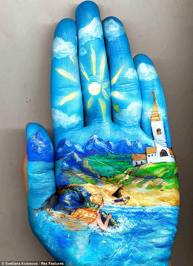 Handy talent: Svetlana Kolosova can spend hours painting the whimsical artwork onto her left hand