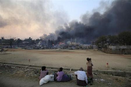 Smoke rises as people look on in Meikhtila, March 21, 2013. REUTERS-Soe Zeya Tun