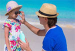 Father applying sunscreen to daughters face