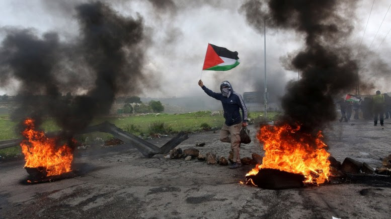 A Palestinian protester waves Palestine flag during clashes marking Land Day in the West Bank City of Ramallah, 30 March 2018. According to reports, 16 Palestinians were killed and more than 1500 injured during the clashes along the Gaza border with Israel. Clashes erupted in various locations in the West Bank and alongside the Israeli borders with Gaza as Palestinians hold protests on the occasion of Land Day, the annual day commemorating the events of 30 March 1976 when marches and a general strike was organized in the Arab towns in the occupied lands. EPA, ALAA BADARNEH