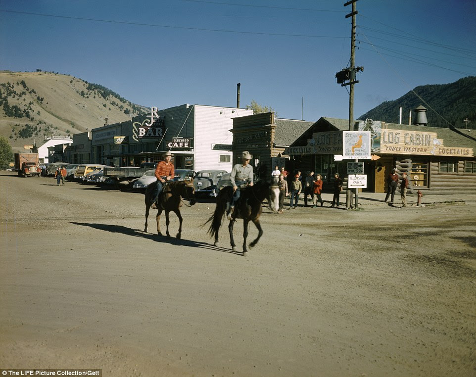 Yee-hah: Two horse riders trot through the ranch on Broadway street in Jackson Hole, with various bars and lounges in the background