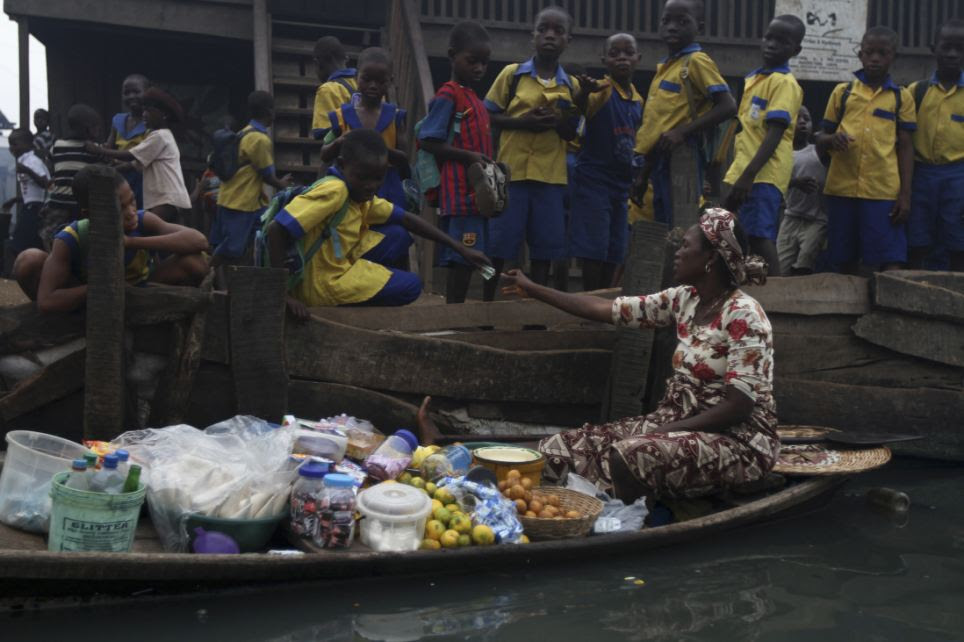 A woman sat in a canoe sells food to school children in front of a makeshift school in Makoko