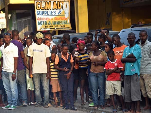 Haitianos observam corpo de homem carbonizado nesta quinta-feira (12) em Petion Ville (Foto: AFP PHOTO/HECTOR RETAMAL)
