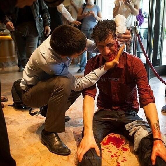 An injured protester stranded inside an hotel waits for an ambulence