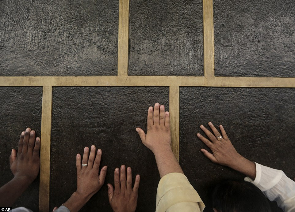 Muslim pilgrims pray while touching the Kaaba. Saudi authorities deploy 100,000 police and vast numbers of stewards to ensure safety and help those who lose their way