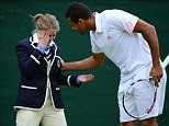 France's Jo-Wilfried Tsonga attends to a line judge who has been hit in the face by a ball during his fourth round men's singles match against U.S. player Mardy Fish on day seven at Wimbledon