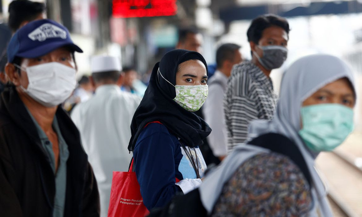 People with surgical masks look on at station Tanah Abang, following the outbreak of the coronavirus in China, in Jakarta