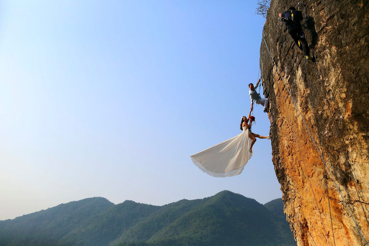 Zheng Feng, an amateur climber takes wedding pictures with his bride on a cliff in Jinhua, China.