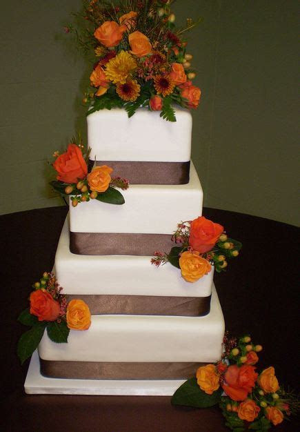 Four tier white wedding cake with brown ribbons and fresh