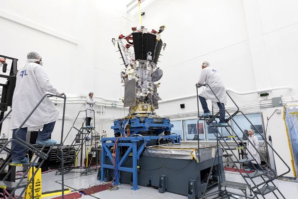 Engineers watch as NASA's Parker Solar Probe spacecraft undergoes vibration testing inside a clean room at the Johns Hopkins University Applied Physics Laboratory.