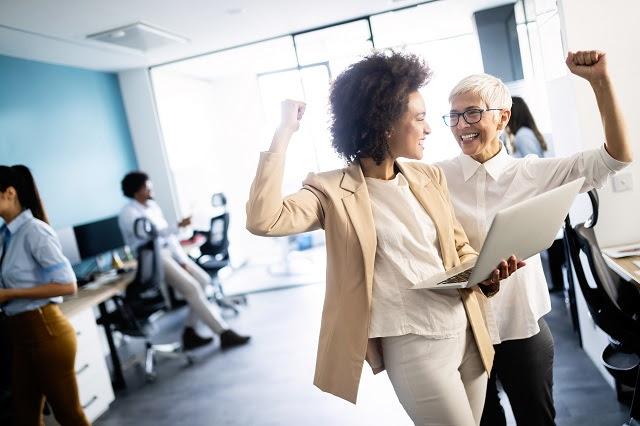 Para-montar-uma-agência-de-marketing-digital-é-preciso-dedicar-se-A-foto-mostra-duas-mulheres-de-diferentes-idades-vibrando-enquanto-trabalham