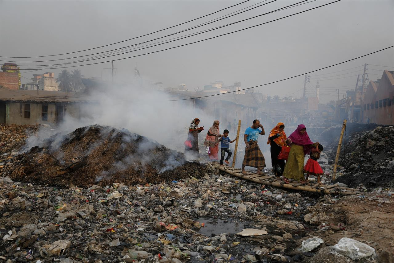 In this Monday, Feb. 6, 2017 photo, Bangladeshi people walk across a temporary bridge as smoke emits from tannery waste at the highly polluted Hazaribagh tannery area in Dhaka, Bangladesh. Pure Earth a nongovernmental organization that addresses industrial pollution put Hazaribagh on its Top 10 list of polluted places, along with Chernobyl, although similar problems of pollution and dangerous working conditions exist at tannery clusters in the Philippines and India as well.