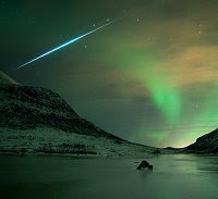 A Geminid meteor streaks through the Northern Lights