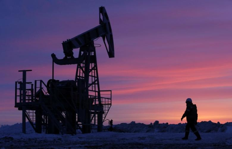 FILE PHOTO: A worker walks past a pump jack on an oil field owned by the Bashneft company near Nikolo-Berezovka, Bashkortostan, Russia , January 28, 2015.   REUTERS/Sergei Karpukhin/File Photo