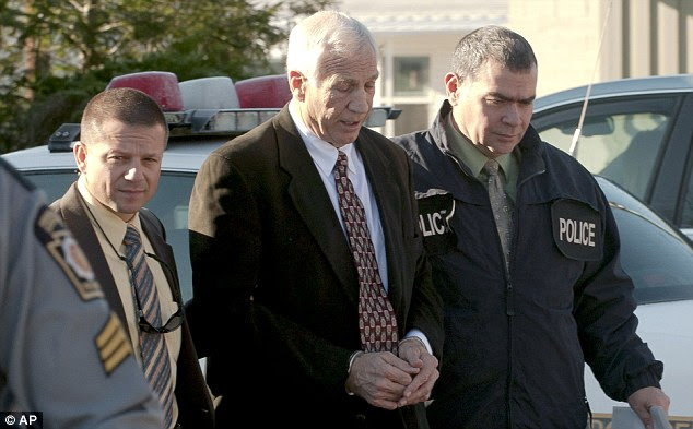 Handcuffed: Eight young men have been identified as the targets of sexual advances or assaults by Sandusky from 1994 to 2009, prosecutors said