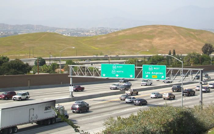 In this photograph that I took on 4/24/08, rush hour traffic begins to form on the 57 and 60 freeways.  Beyond them are the hills, nicknamed 'The Boonies', where the Los Angeles Football Stadium would be located if it was built.
