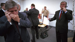"Bush confers on a secure line as ""the football"" -- the briefcase holding the secure nuclear launch codes -- is watched by a Marine."