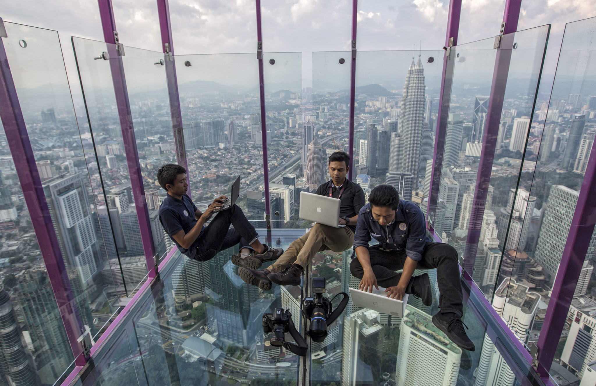 Media members sit against the panoramic view of Kuala Lumpur from a skybox during a media preview at Kuala Lumpur Tower in Kuala Lumpur, Malaysia, 05 May 2016. Skybox, 421 metres above ground level will be the latest tourists attraction at Kuala Lumpur Tower, the 7th tallest freestanding tower in the world.