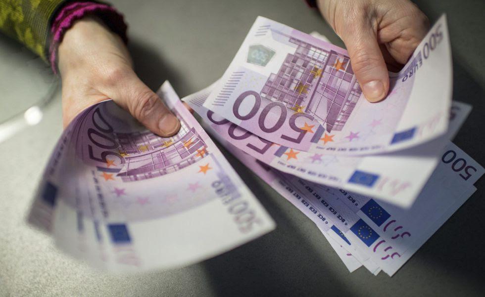 Un empleado de banca muestra billetes de 500 en una sucursal del banco Sparkasse en Múnich (Alemania).